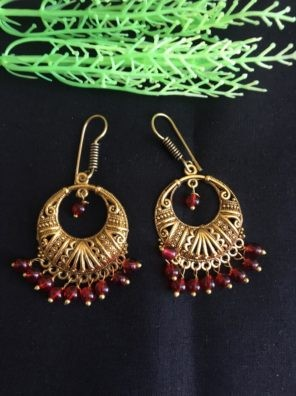Gold earring with red pearl